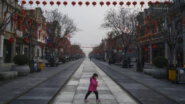 Menina de máscara no rosto atravessa rua vazia na China
