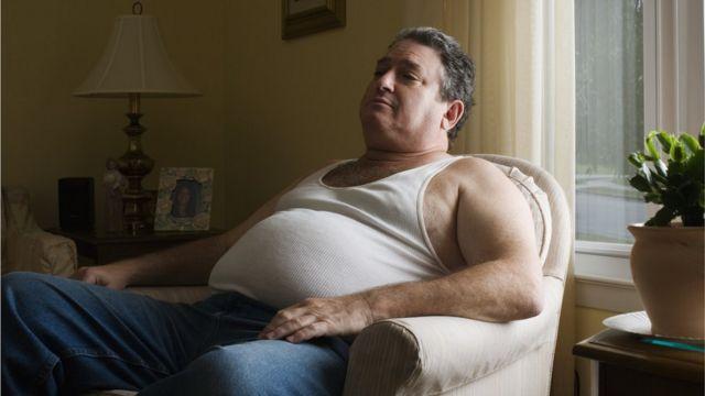 Homem obeso sentado no sofá