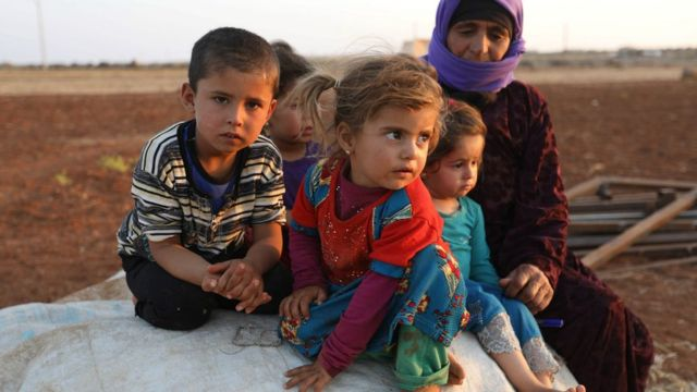 Syrian children sit next to a woman at a camp for displaced civilians near the village of Sarman in Idlib province on September 1, 2018