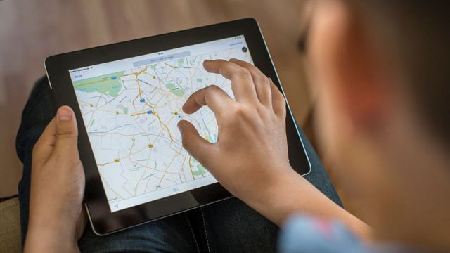 Joven con Google Maps en un iPad.