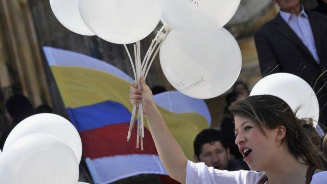 Mujer con globos blancos y bandera de Colombia