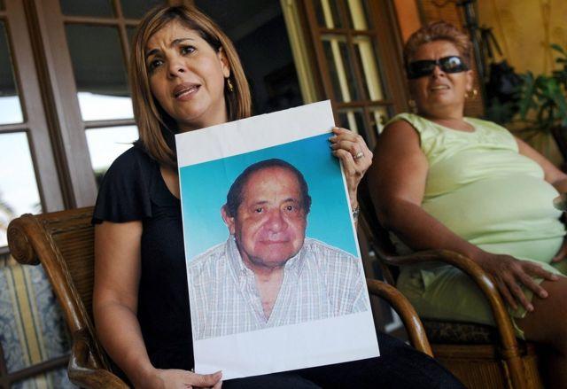 """Mitzila Donado (izquierda), junto a su madre Rudecinda Delgado, sostiene una foto de su padre, Jaime Donaldo, quien murió en 2006 tras haber tomado el """"jarabe de la muerte"""". Imagen tomada el 25 de marzo de 2009 en Ciudad de Panamá. (Foto: Elmer Martínez / AFP / Getty Images)"""