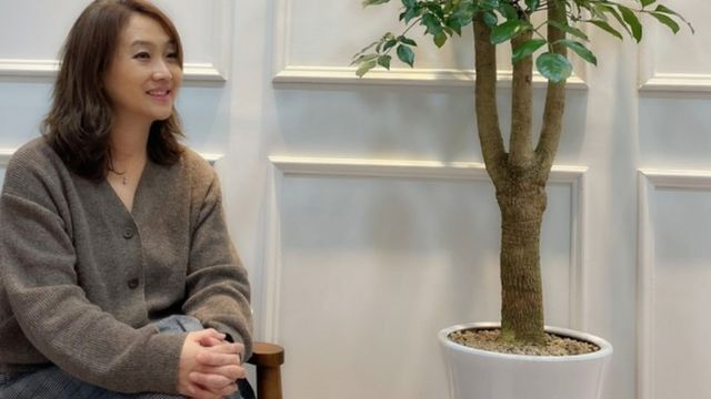 Julia Yoon sits on a chair next to a plant.