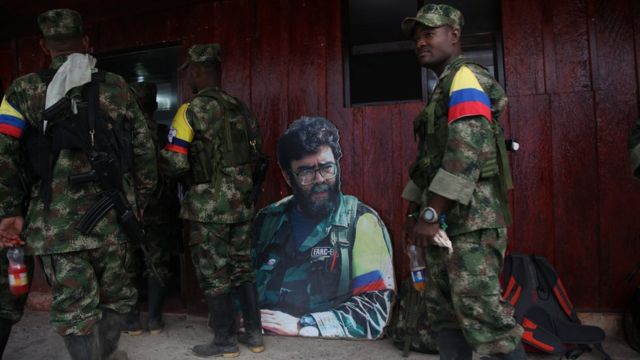 Un Alfonso Cano recortado en cartón observa a los guerrilleros recién llegados.