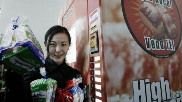 2004年3月25日,一位营销主管在展示新加坡自动售货机出售的一些面包。