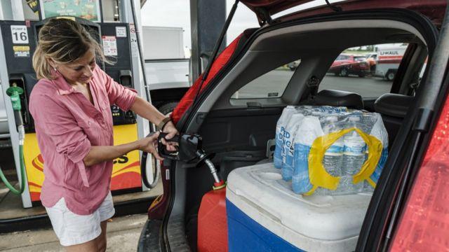 A woman filling a gallon of gasoline