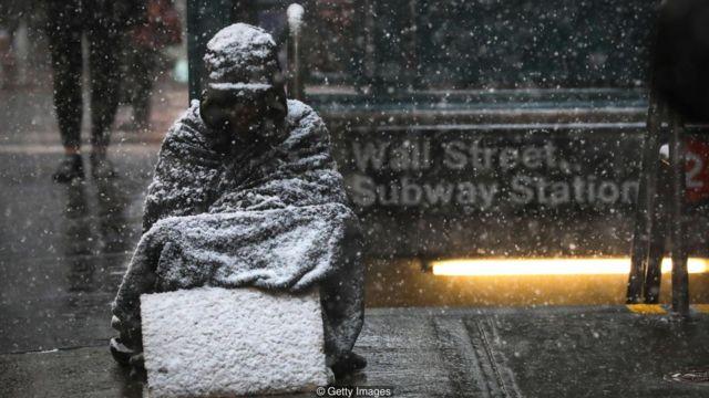Imagem mostra possível morador de rua sentado em meio à nevasca