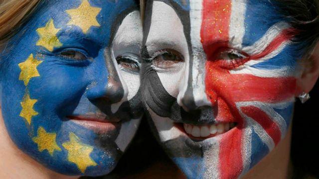 Dos jóvenes con los rostros pintados con los colores de las banderas de la Unión Europea y el Reino Unido