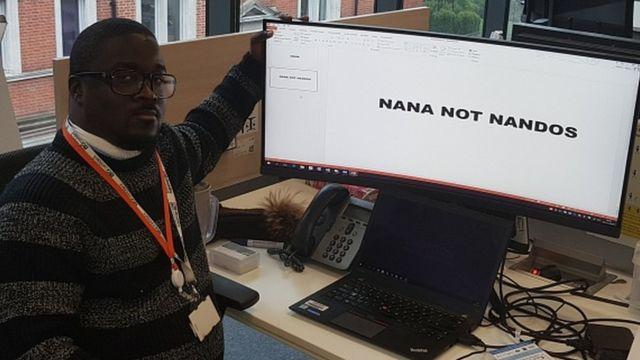 "Nana Marfo sits next to his computer which states ""Nana not Nandos"""