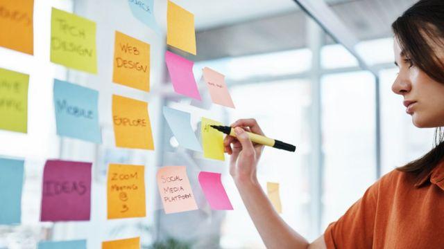 Mujer escribiendo en papeletas autoadhesivas o post its.