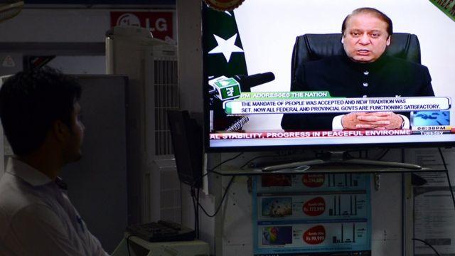 ایک شخص ٹی وی پر نواز شریف کا خطاب دیکھ رہا ہے