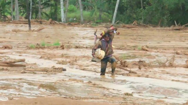 man carrying possessions through mud
