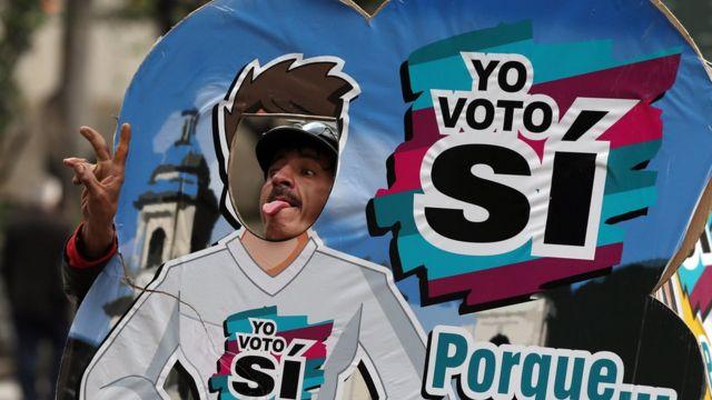 """Homem posa para foto ao lado de cartaz do """"sim"""" em Bogotá, na Colômbia"""