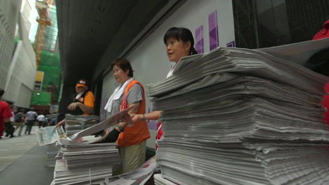 Women handing out newspapers in Hong Kong