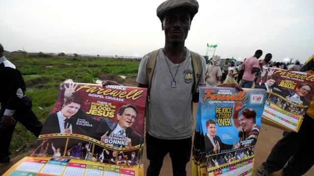 """Un marchand vend des affiches avec des photos de l'évangéliste pentecôtiste allemand Reinhard Bonnke et de son successeur Daniel Kolenda avant la """"croisade d'adieu"""" de Reinhard Bonnke, le 9 novembre 2017 à Lagos."""