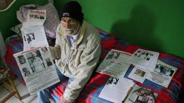 Leonardo da Cruz, pai de Robson, sentado em sua cama, ao lado de sete tipos diferentes de cartazes que colou pela Grande São Paulo em busca do filho