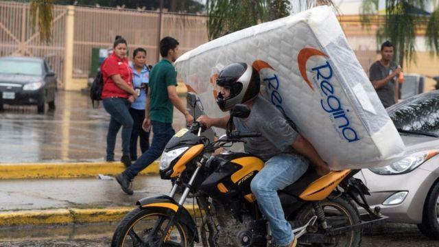 un hombre se lleva un colchón en una moto en Honduras