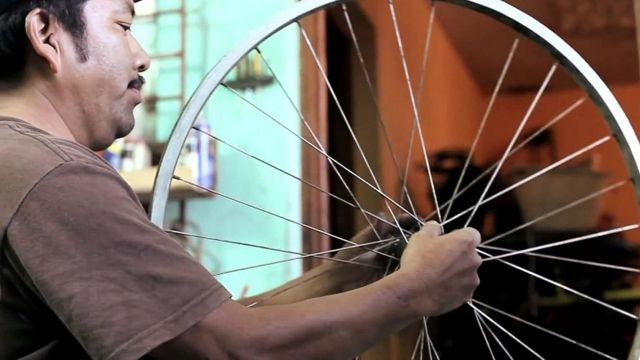 Guatemalan man making a bicycle machine from a second-hand bicycle
