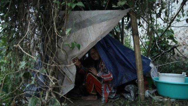 """A refugee from Myanmar rests in a temporary shelter in Wanding, in China""""s southwest Yunnan province on November 30, 2016."""