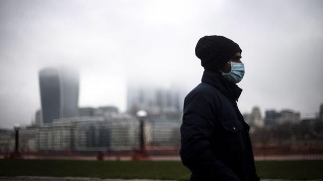 Un hombre camina por Londres con una máscara.
