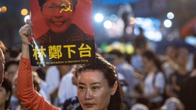 A woman holds a poster of Hong Kong Chief Executive Carrie Lam, against a proposed extradition law