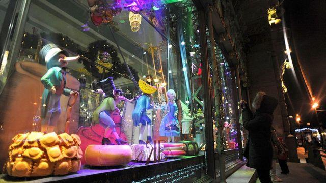 Transeunte tira foto da vitrine decorada da mercearia Yeliseyevsky no centro de São Petersburgo, em 12 de dezembro de 2012