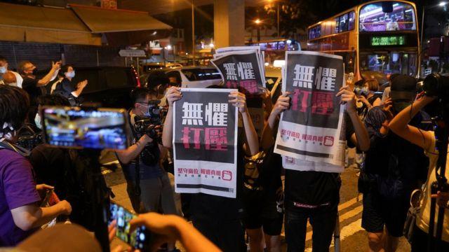 黎智英支持者在九龙旺角警署外举起《苹果日报》声援(12/8/2020)