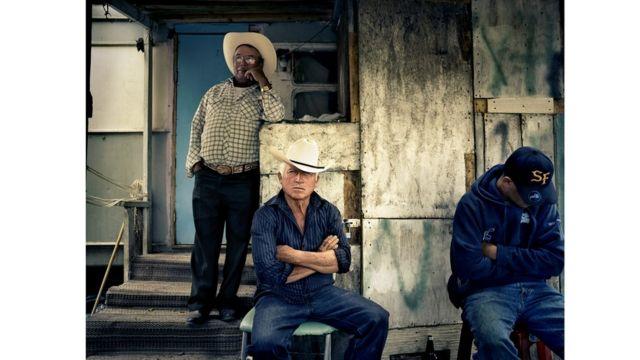 Tres hombres sentados fuera de una construcción.