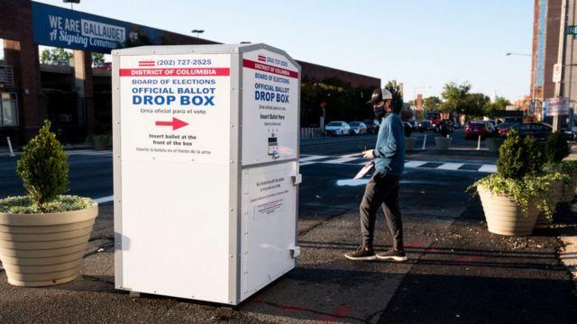 Una persona depositando su voto por correo