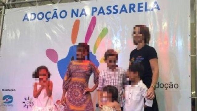 Crianças e uma mulher adulta posam em frente a painel com os dizeres: Adoção na passarela