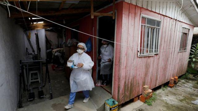 Duas profissionais de jaleco saem pela porta de uma casa