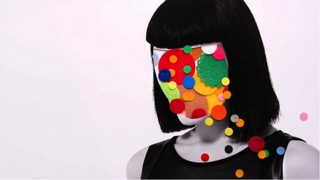 A woman in black and white with colours all over her face