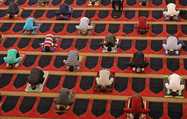 Worshippers pray whilst social distancing