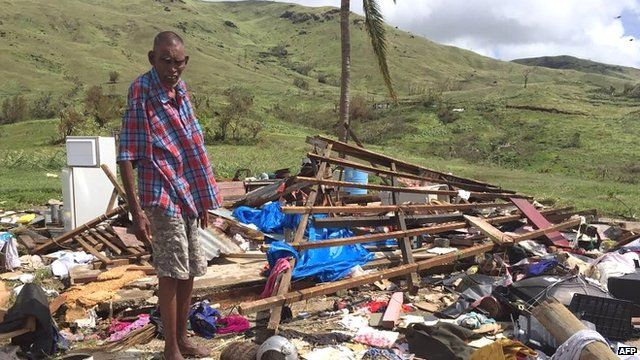 Man stands over ruins of his house in Fiji