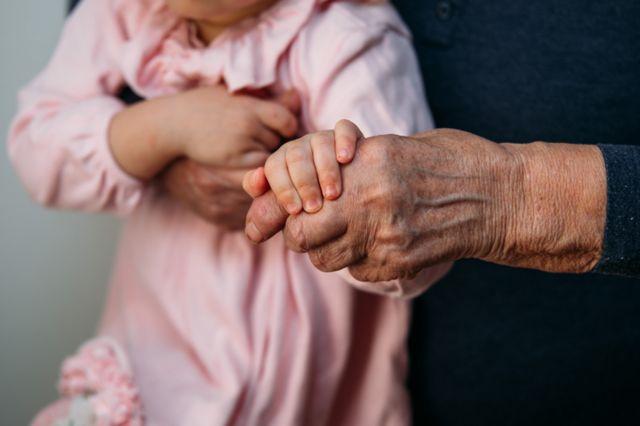 Adulto mayor sosteniendo a un niño.