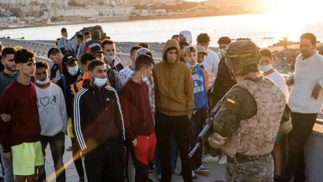 Spanish army officer talks with young migrants.
