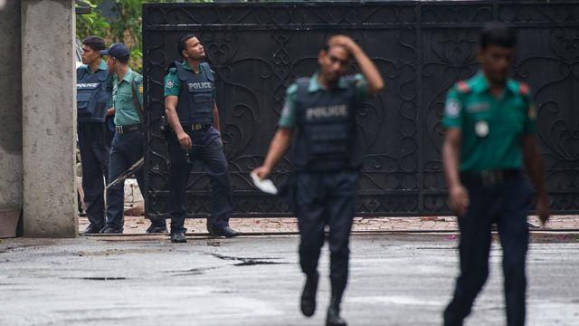 襲撃されたカフェ前のゲートから出てくる警官たち(3日)