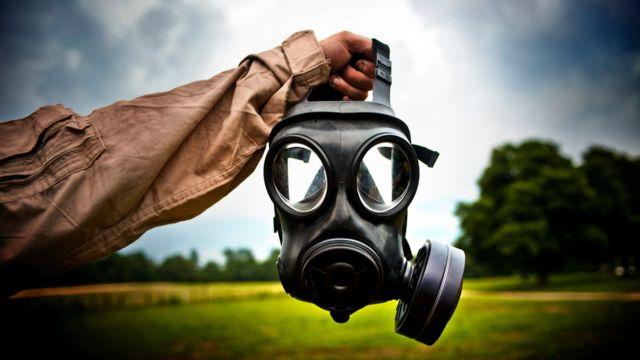 Braço segura máscara em ambiente ao ar livre