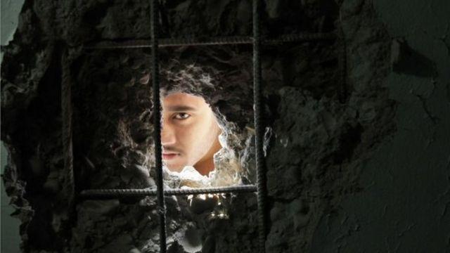 मोर्टार बम से टूटी दीवार से झांकता एक लड़का