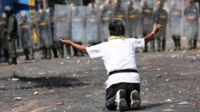 یک معترض در برابر صف گارد ضدشورش در شهر یورنا زانو زده