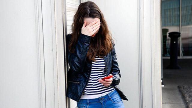 Adolescentes com mão sobre os olhos e cabeça abaixada