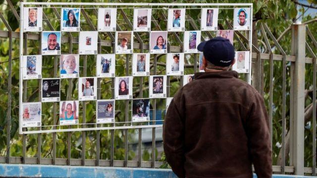 Homem de costas observa mural de fotos em grade (aparentemente de um parque)