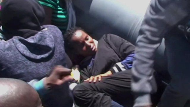 A migrant crammed into the bottom of a dinghy.