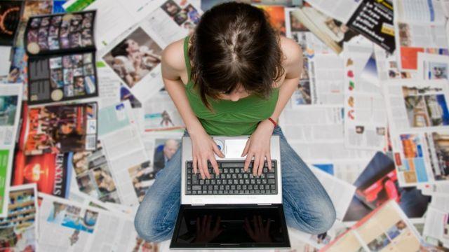Mulher sentada no chão usando laptop rodeada por revistas e jornais