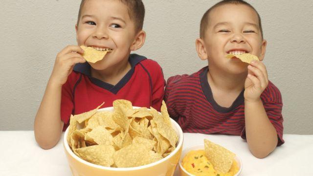 Two boys eating crisps