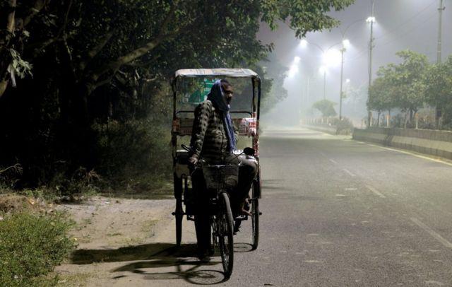 A rickshaw puller in smog