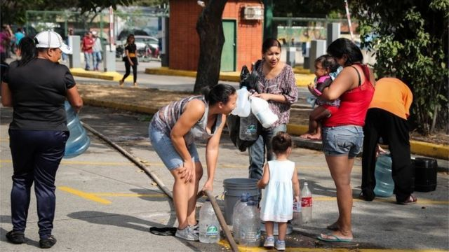 People collect water at the Park of the East, in Caracas, Venezuela, 12 March 2019