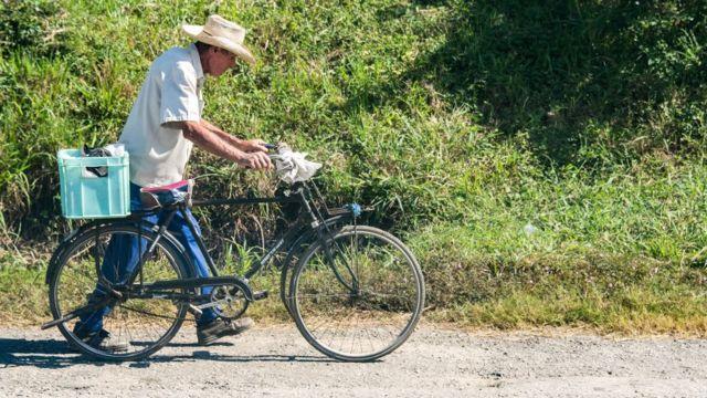 Un hombre lleva una bicileta en Cuba