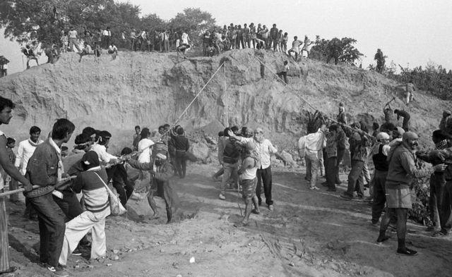 માટીના મોટા ઢગલાને ગબડાવવાનો પ્રયાસ કરતા લોકોને બરાડીને આદેશ આપી રહેલો પુરુષ