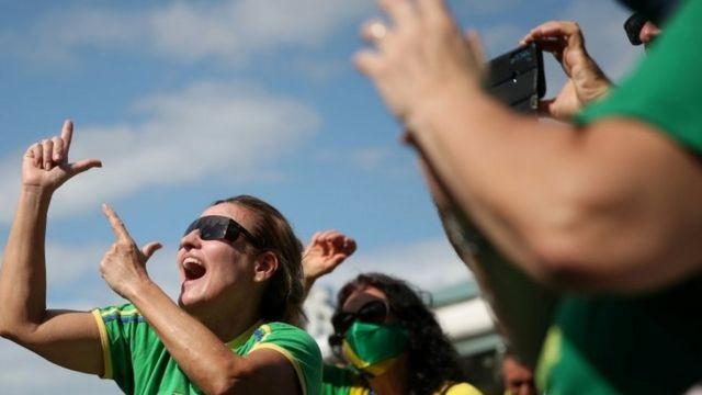 Manifestante vestida com cores do Brasil faz 'arminha' com as mãos